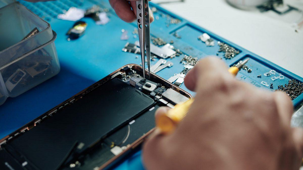 Repairman fixing smartphone camera